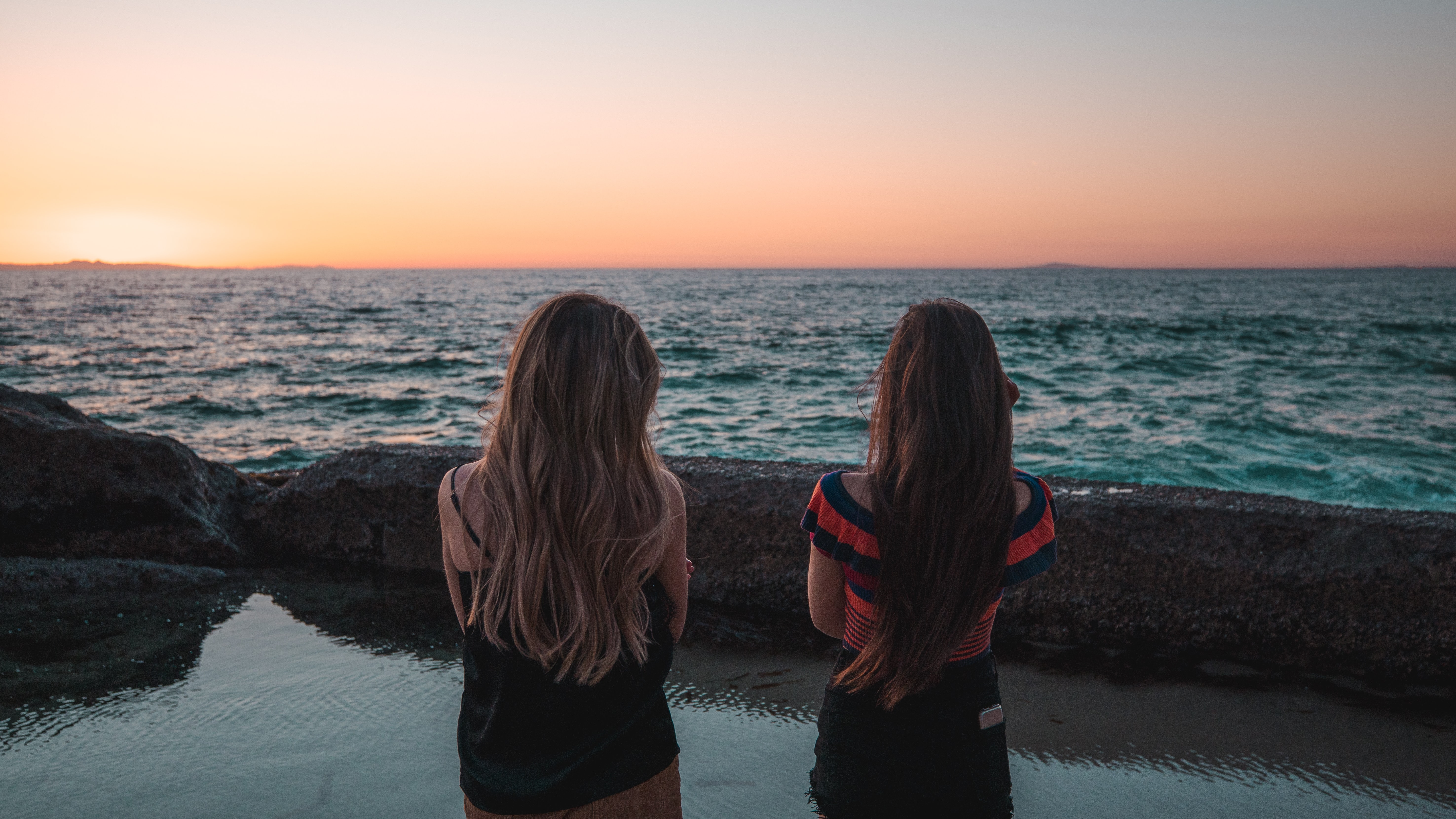 two woman standing facing body of water during daytime