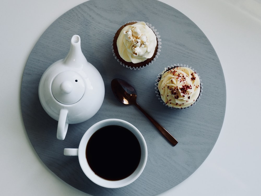 white ceramic teapot beside brown spoon