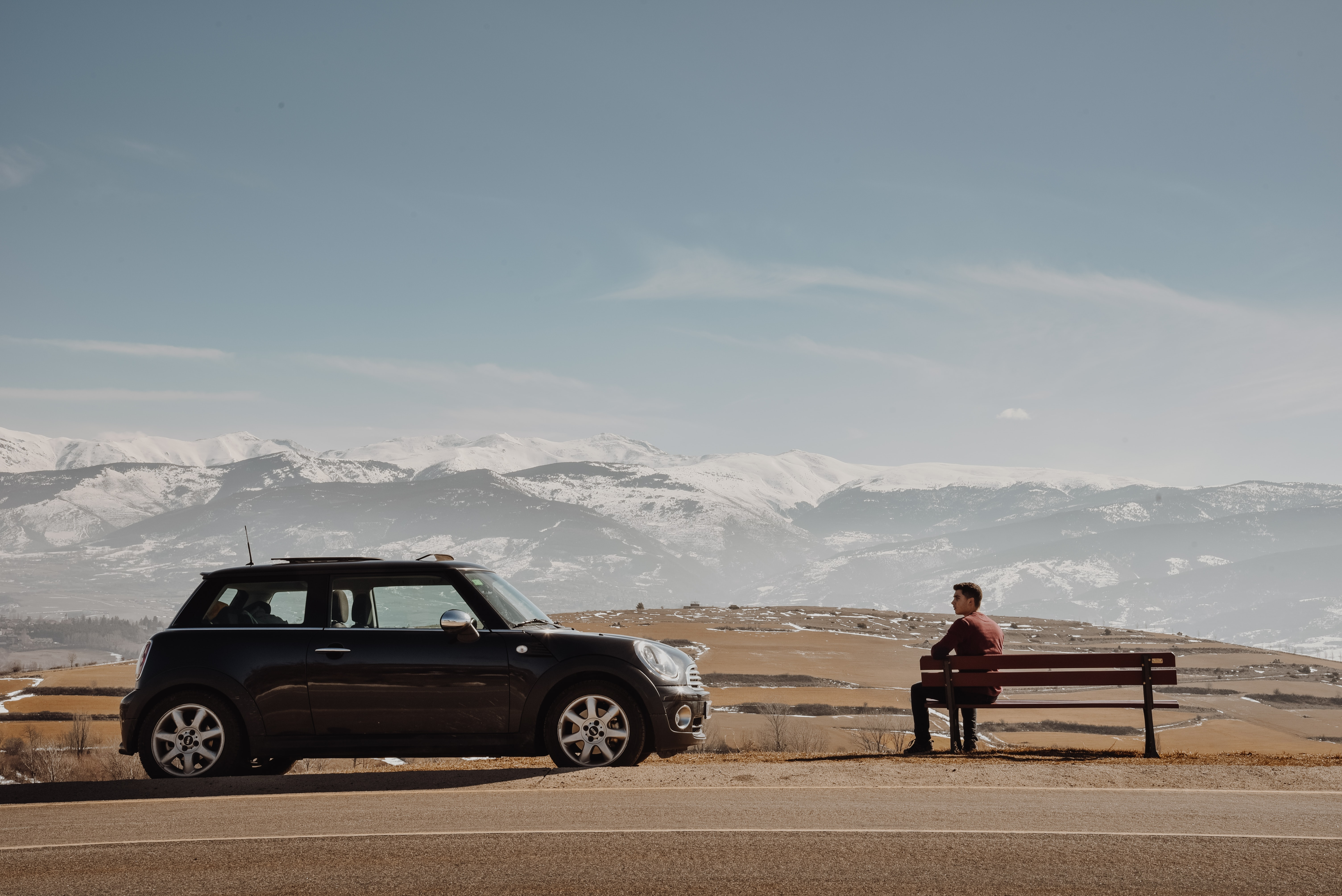 man sitting on the bench near black 5-door hatchback overlooking snow-capped mountains