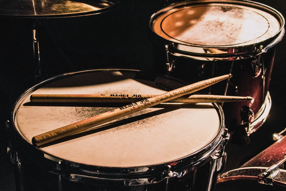 pair of brown wooden drumsticks on top of white and gray musical drum