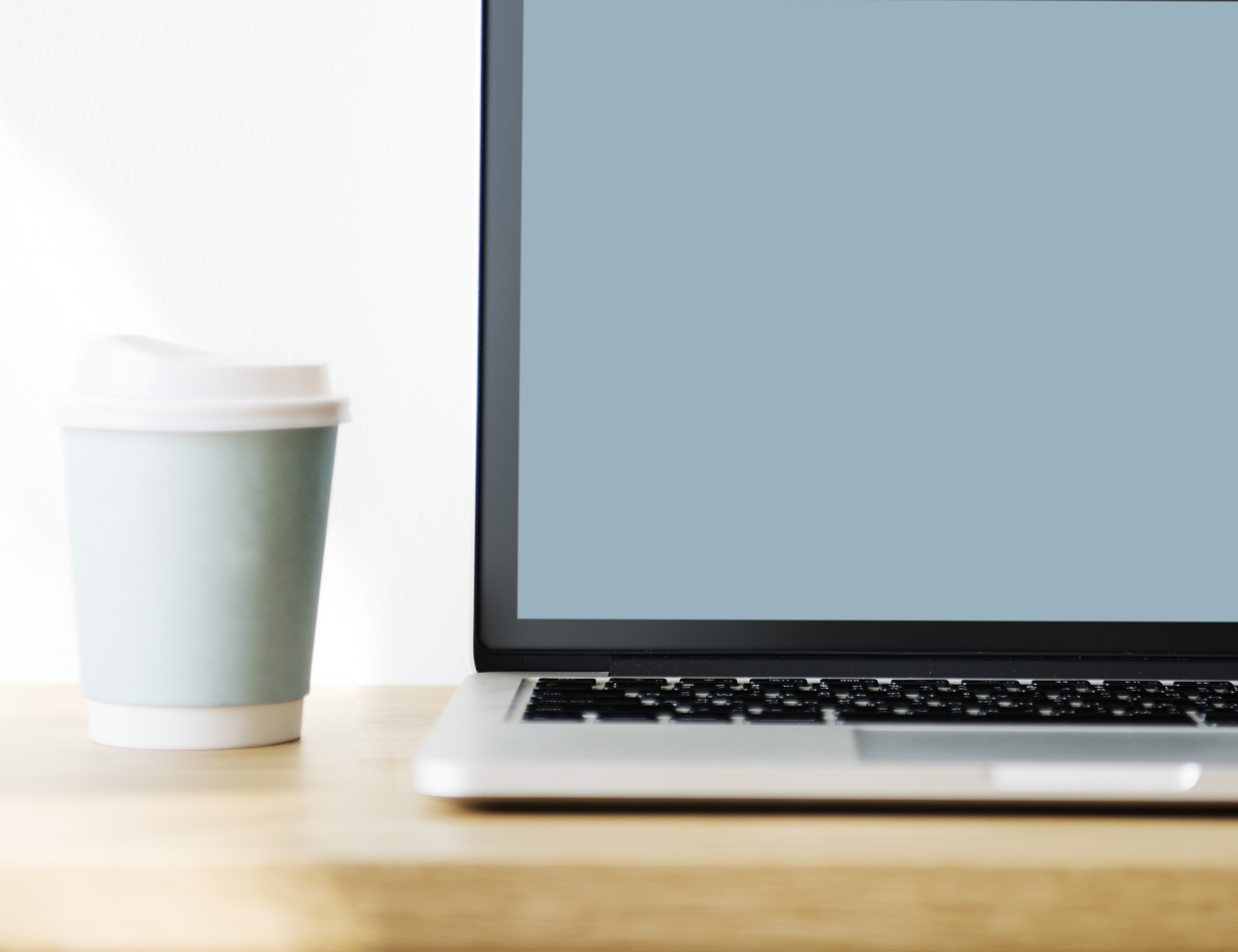 silver laptop near white plastic cup