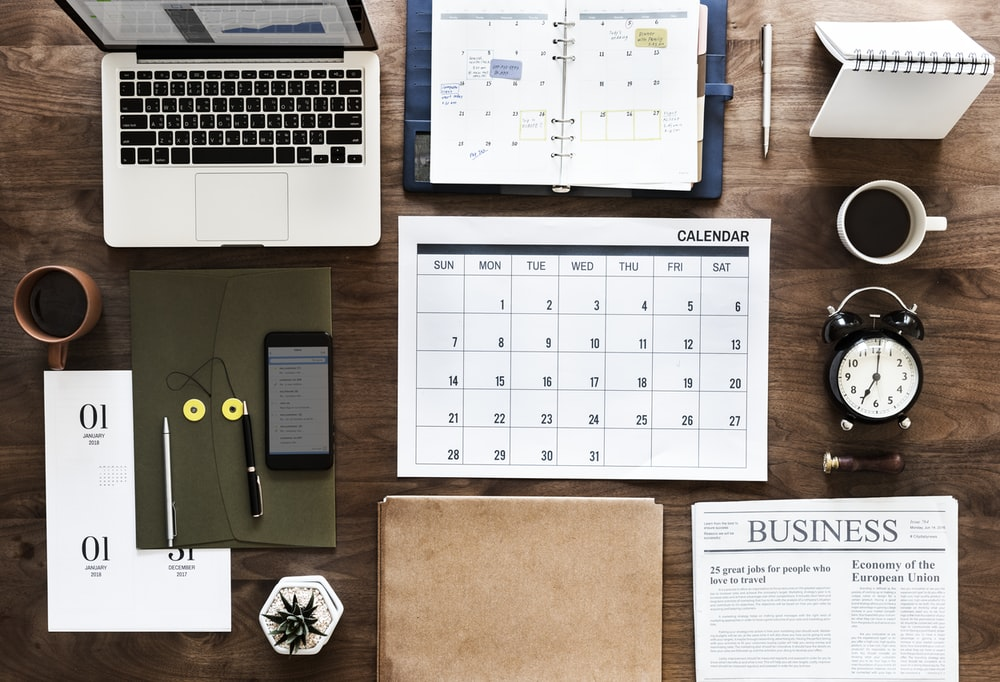 space gray MacBook Pro, Calendar chart, and Business magazine on table