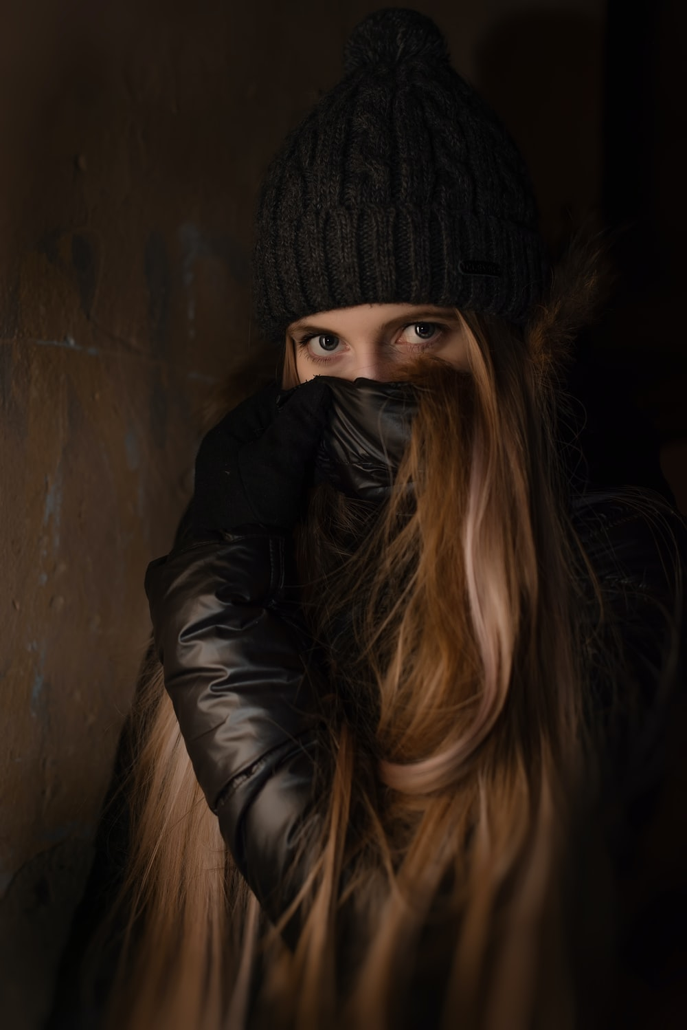 woman covering her face using jacket