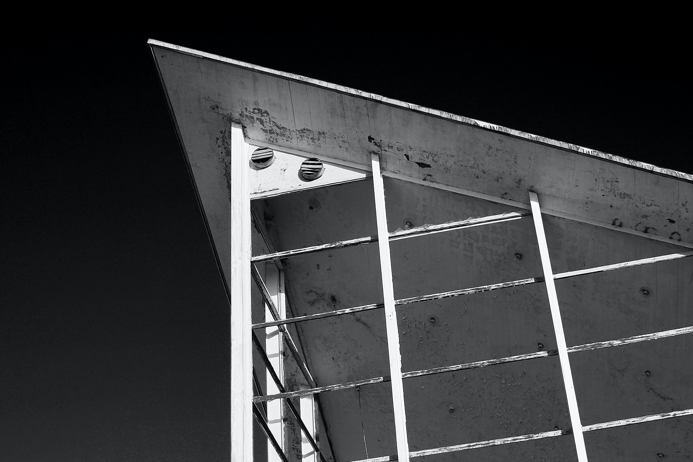 grayscale photography of metal arch roofg
