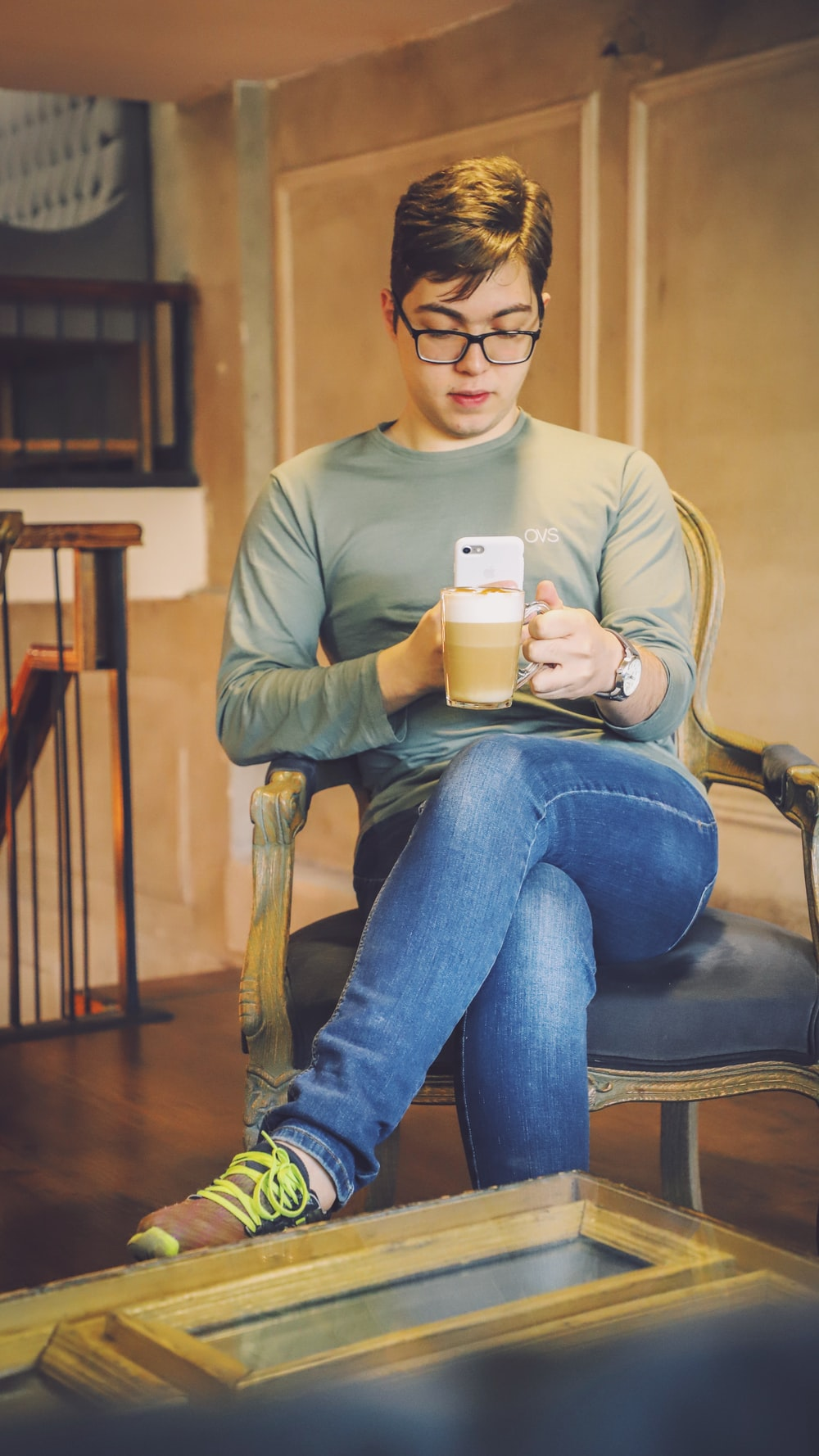 man sitting on brown armchair while taking photo of a cup