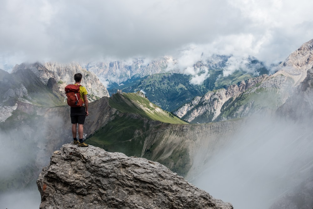man with red backpack standing on cliff facing mountains under white sky during daytime