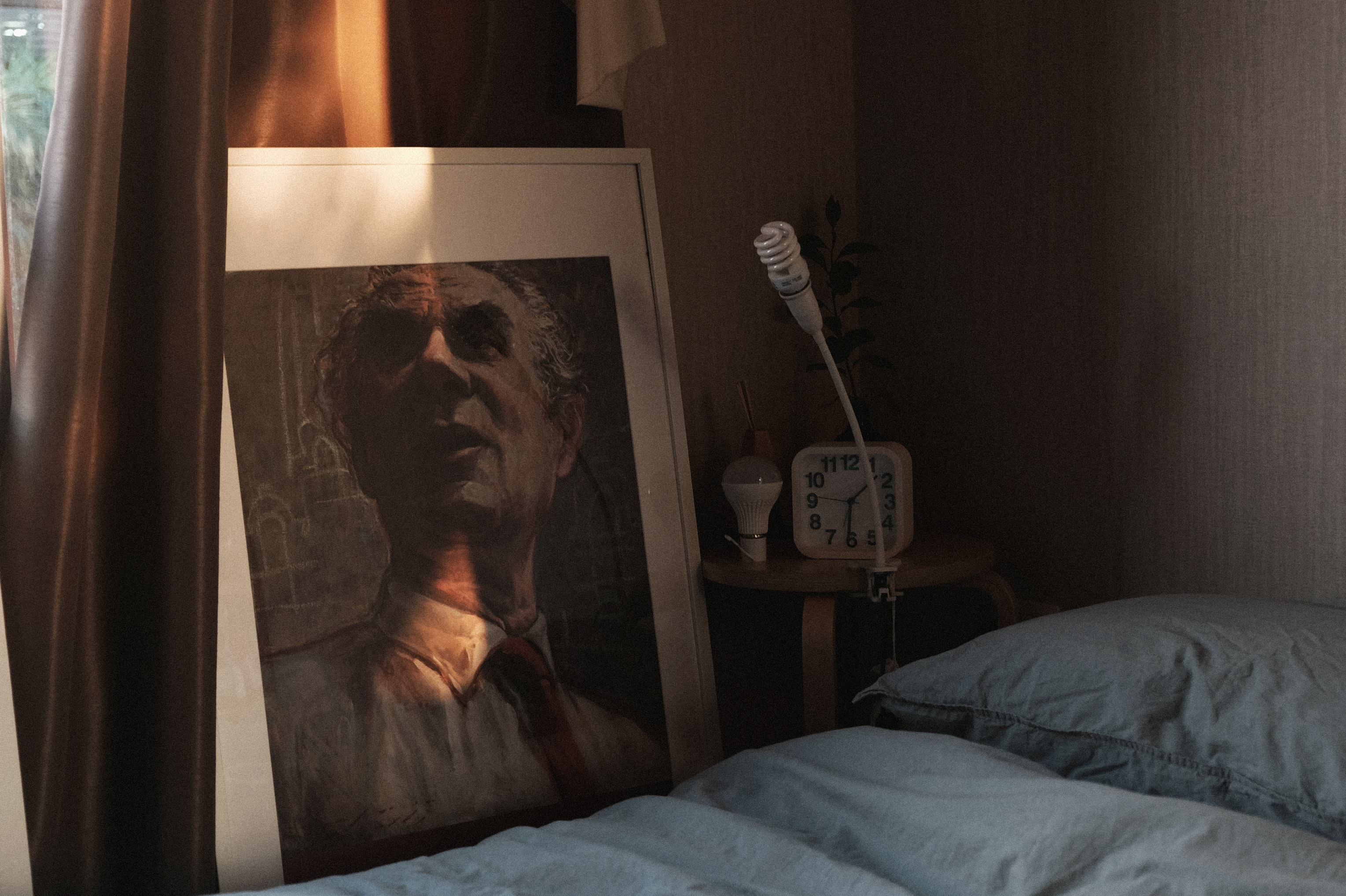 painting of man leaning against window beside bed