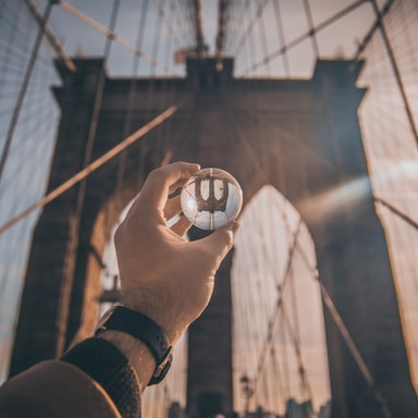man holding ball facing Brooklyn Bridge, New York