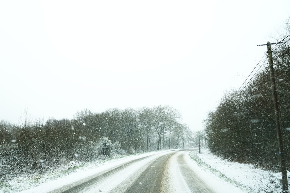 empty winding road surrounded by snow