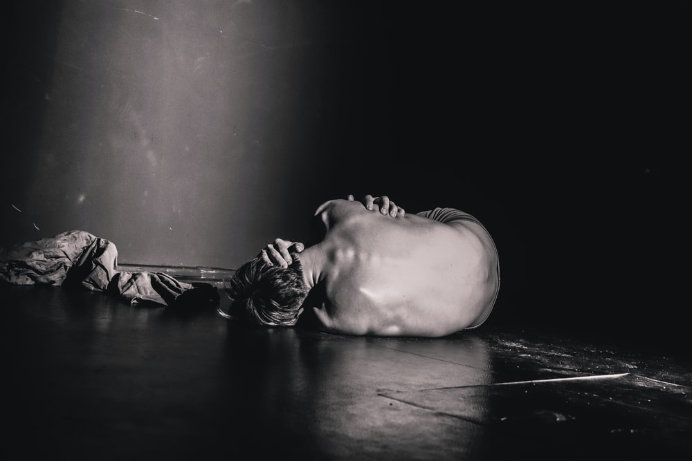 grayscale photography of man lying on floor