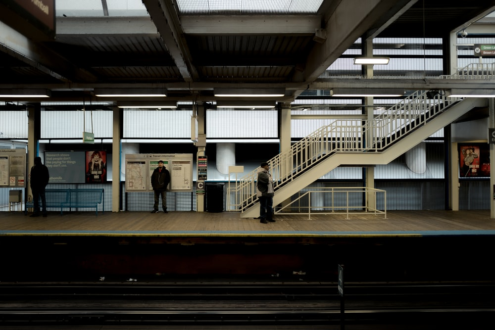 three person waiting on train station