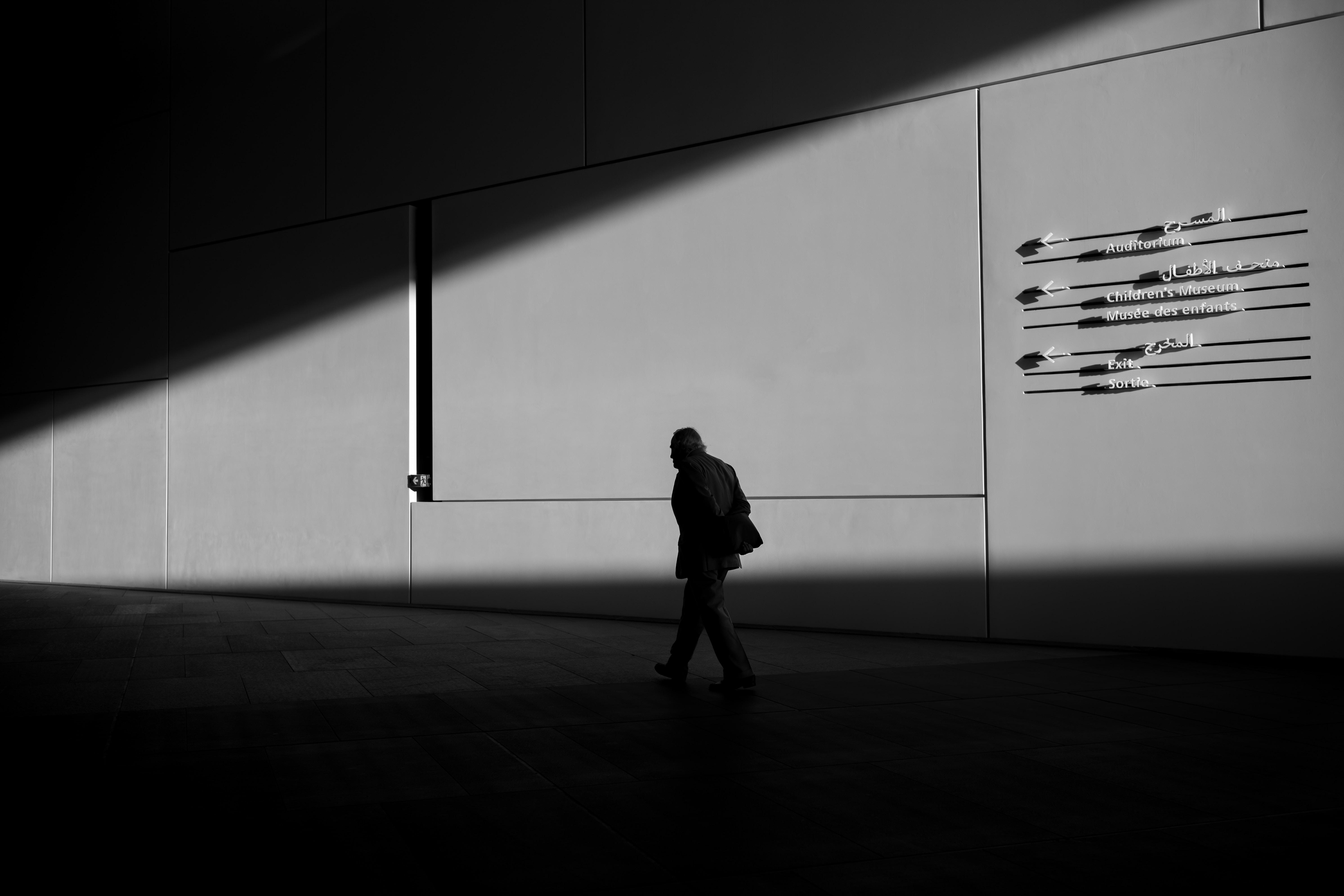 silhouette of man walking on pathway