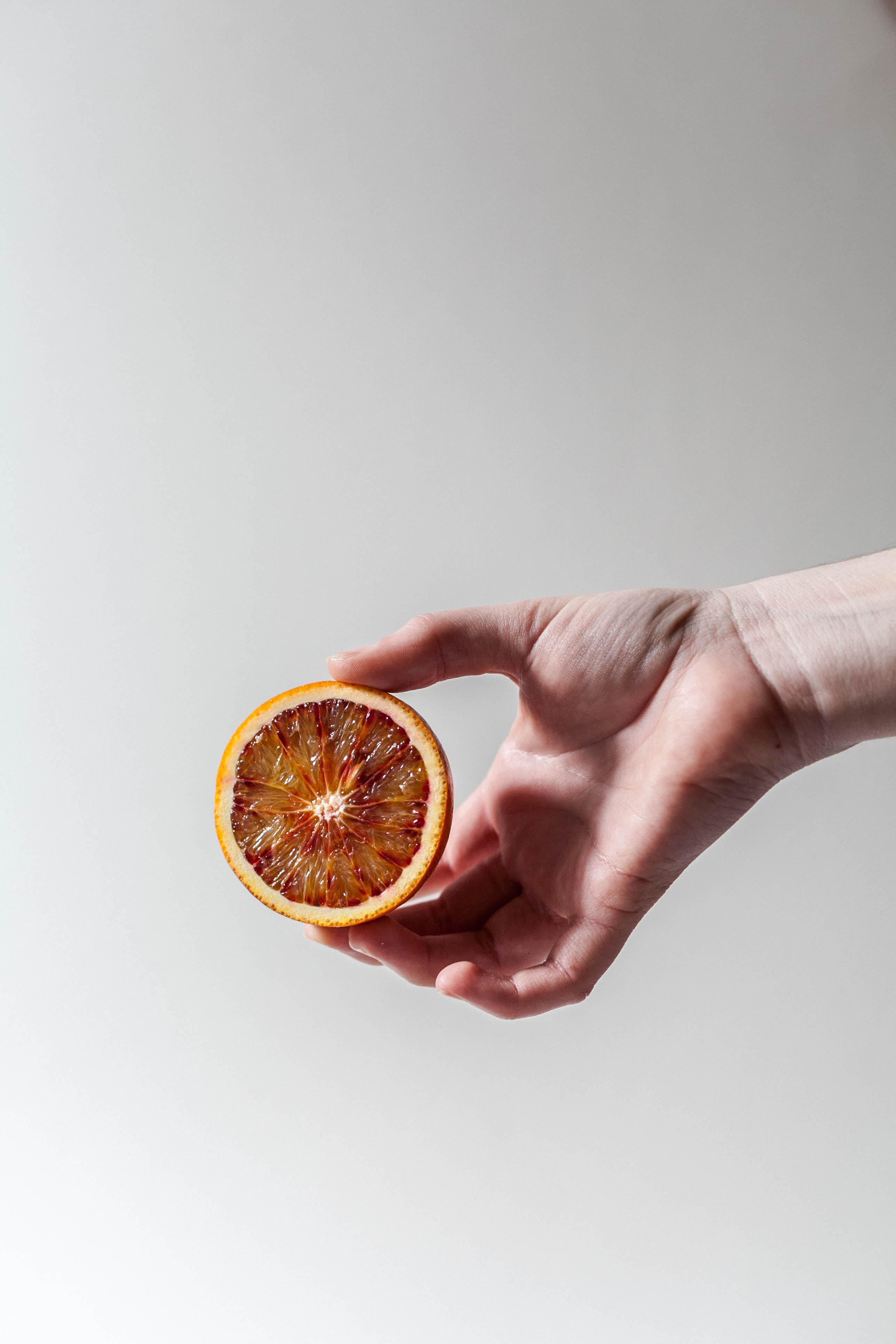 person holding sliced grapefruit