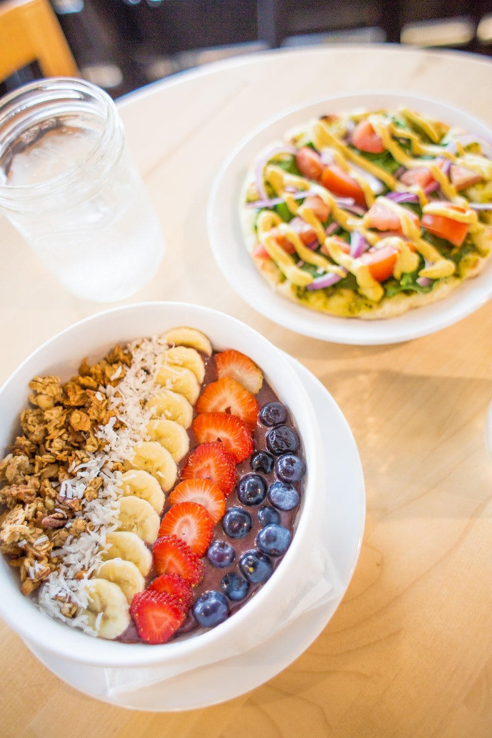 slice banana, strawberry and blueberries on white bowl beside vegetable salad on table