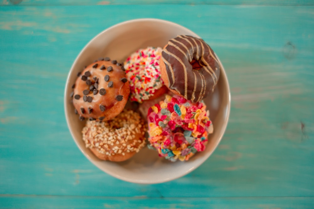 seven assorted-flavor doughnuts on brown ceramic bowl