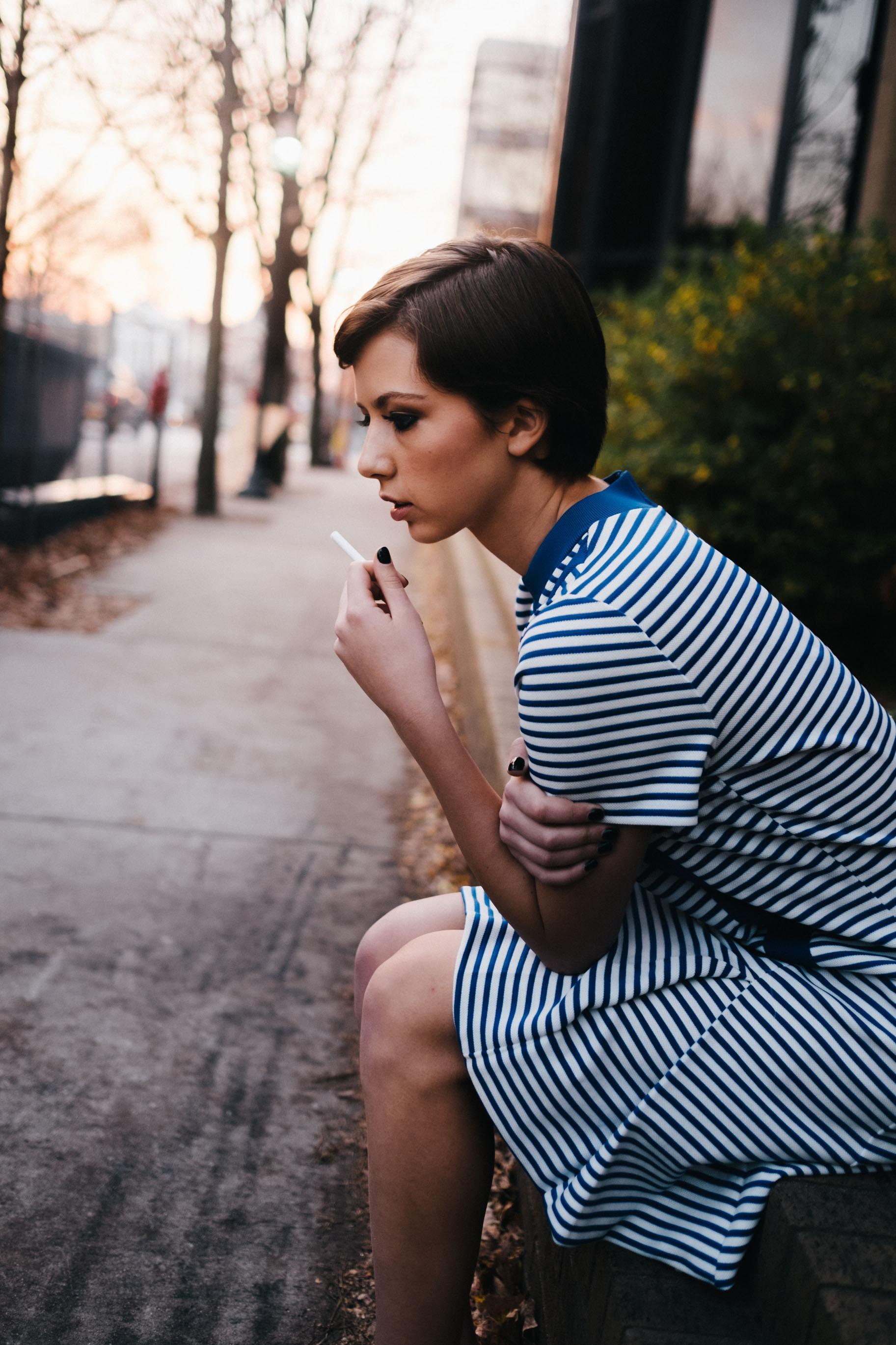 woman sitting down while smoking cigarette