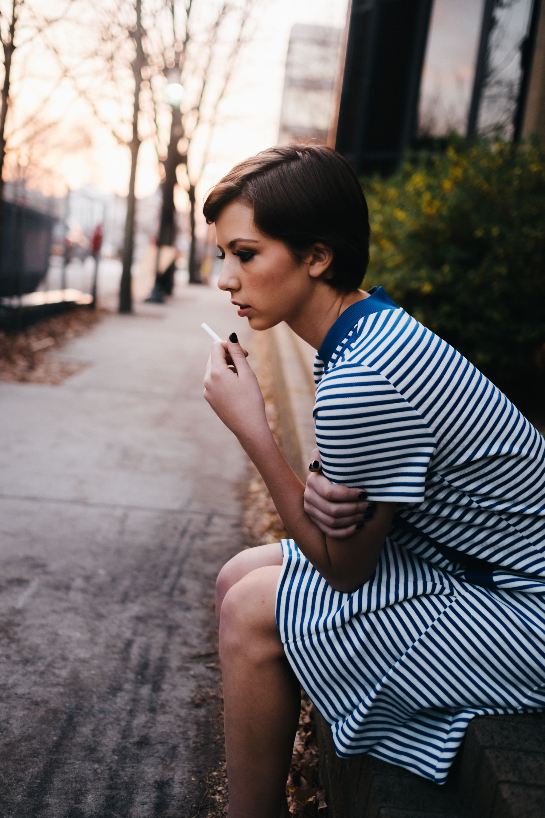 woman sitting down while smoking cigarette