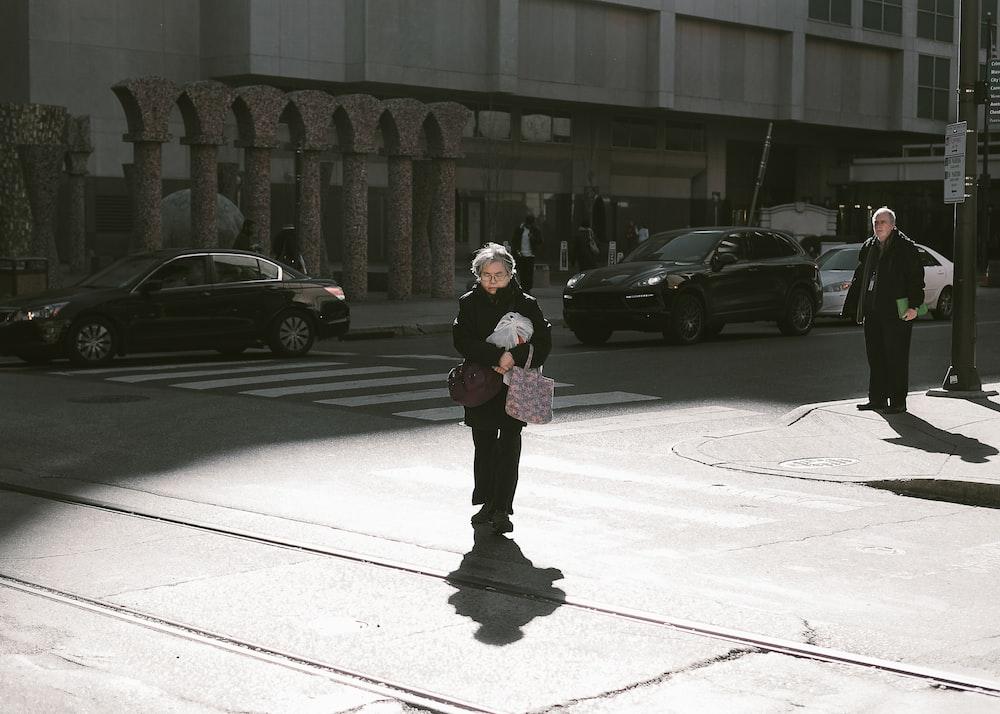 woman walking along street wearing black coat