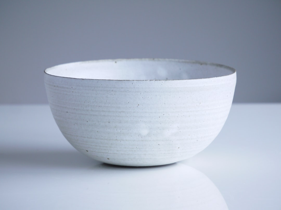 This bowl is made of black clay and covered in a white frost glaze, I've taken the phot on our dining table at home. We have large floor to ceiling windows that are north facing, so we get a soft light, that is actually the most beautiful on a slightly grey day.