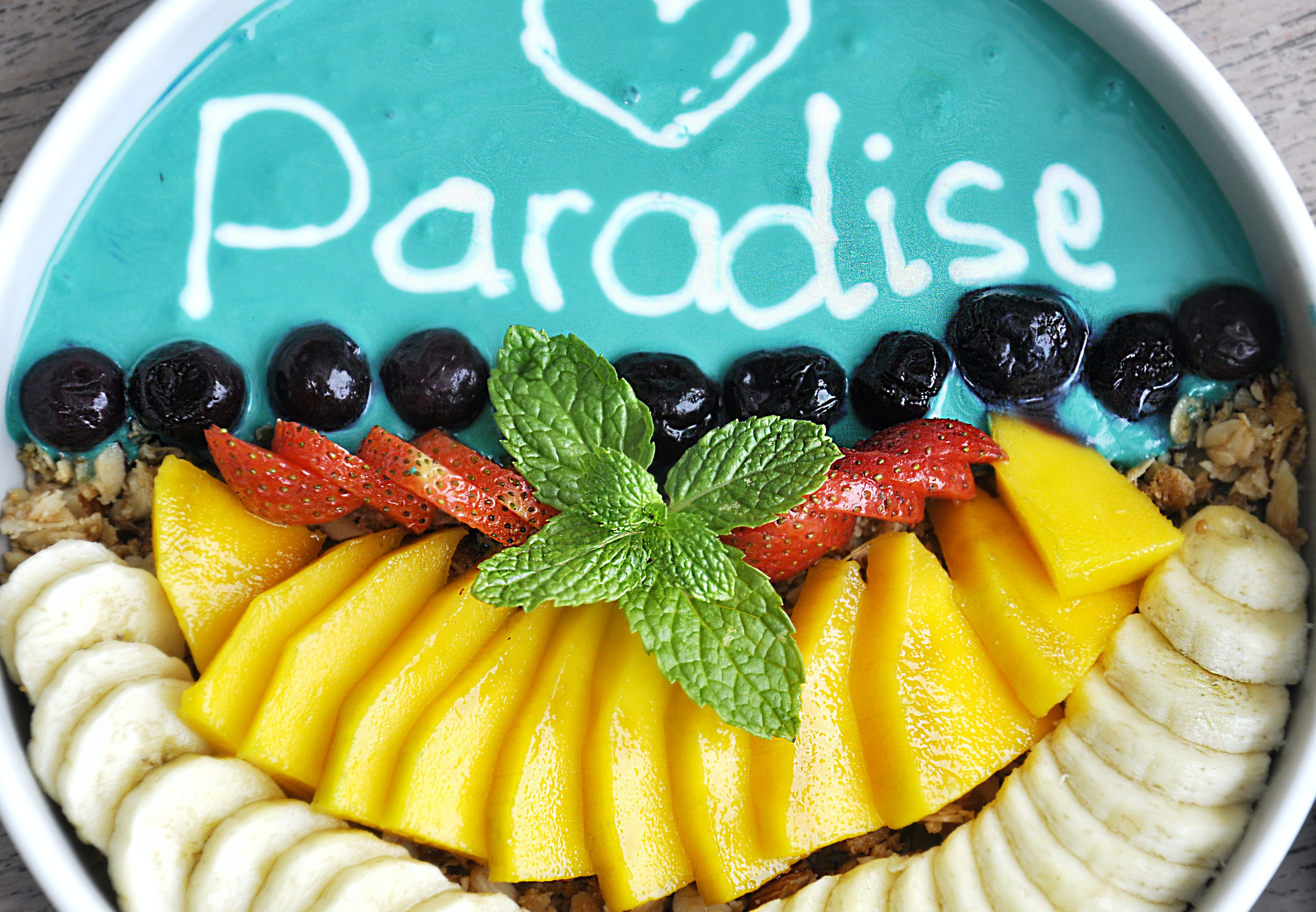 variety of sliced fruits on top of white and teal container