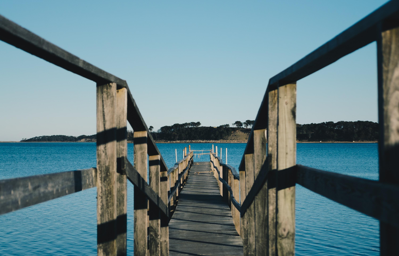 empty brown wooden sea dock under blue sky