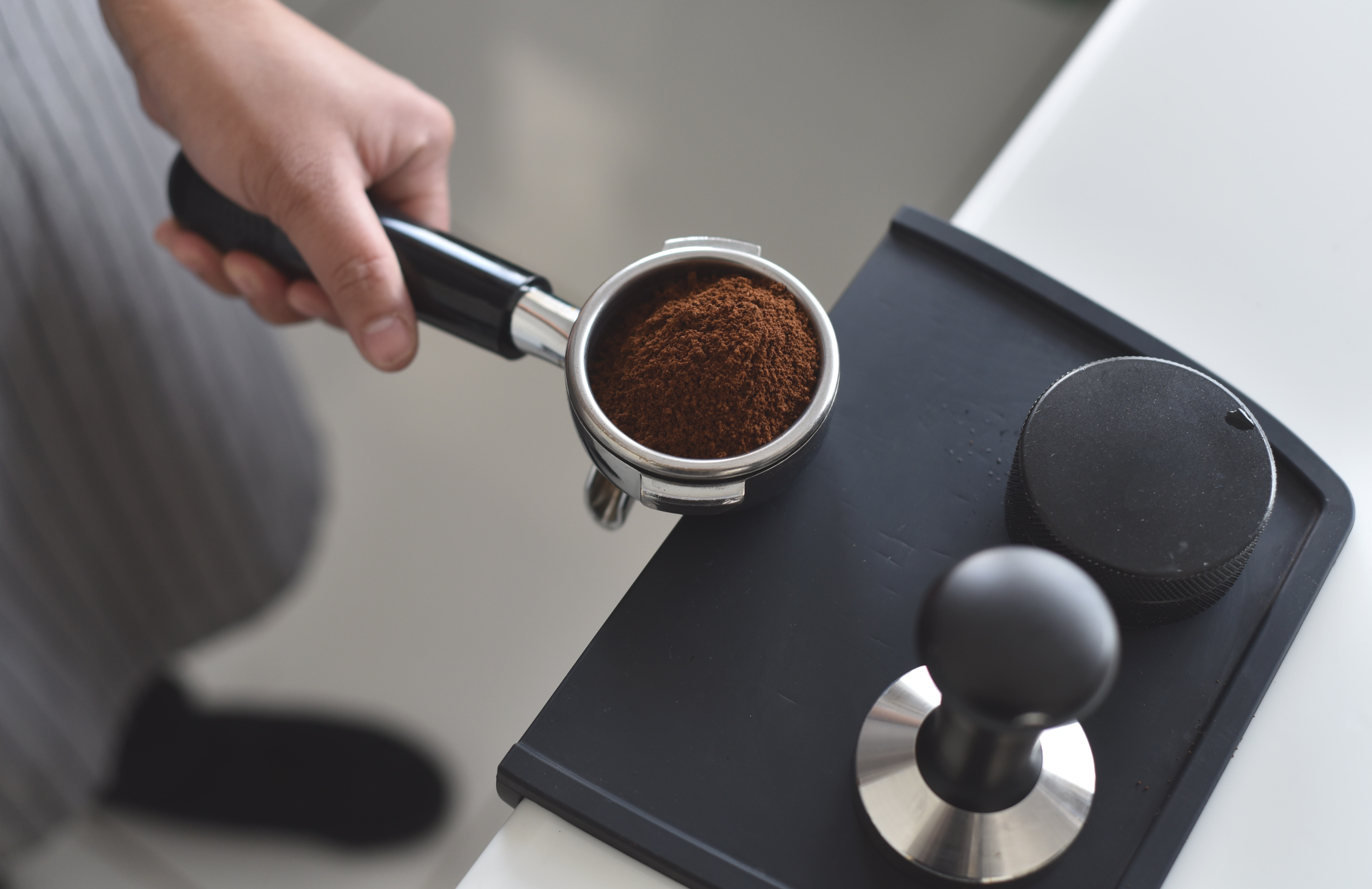 person holding pot with coffee powder