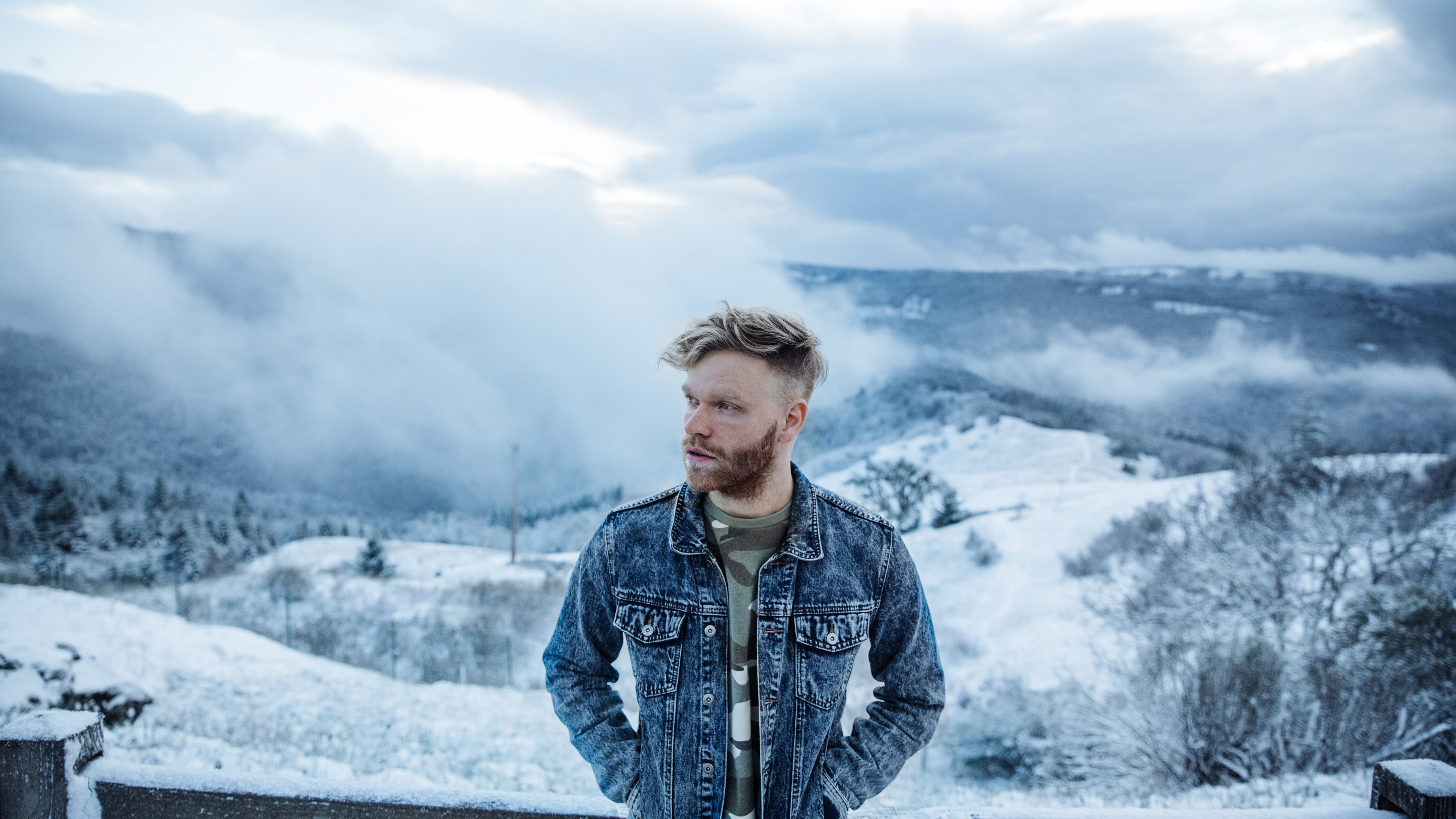 man standing in front of snow mountain