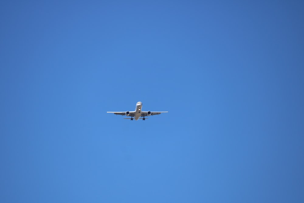 low angle photography of gray airplane under blue sky at daytime