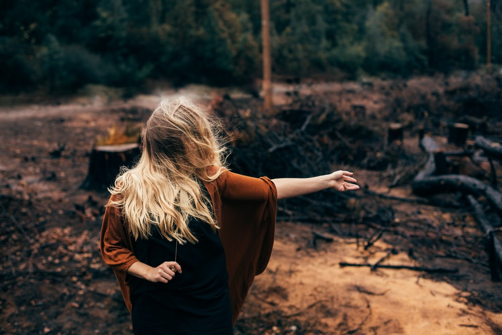 woman standing in front of burned and cut trees