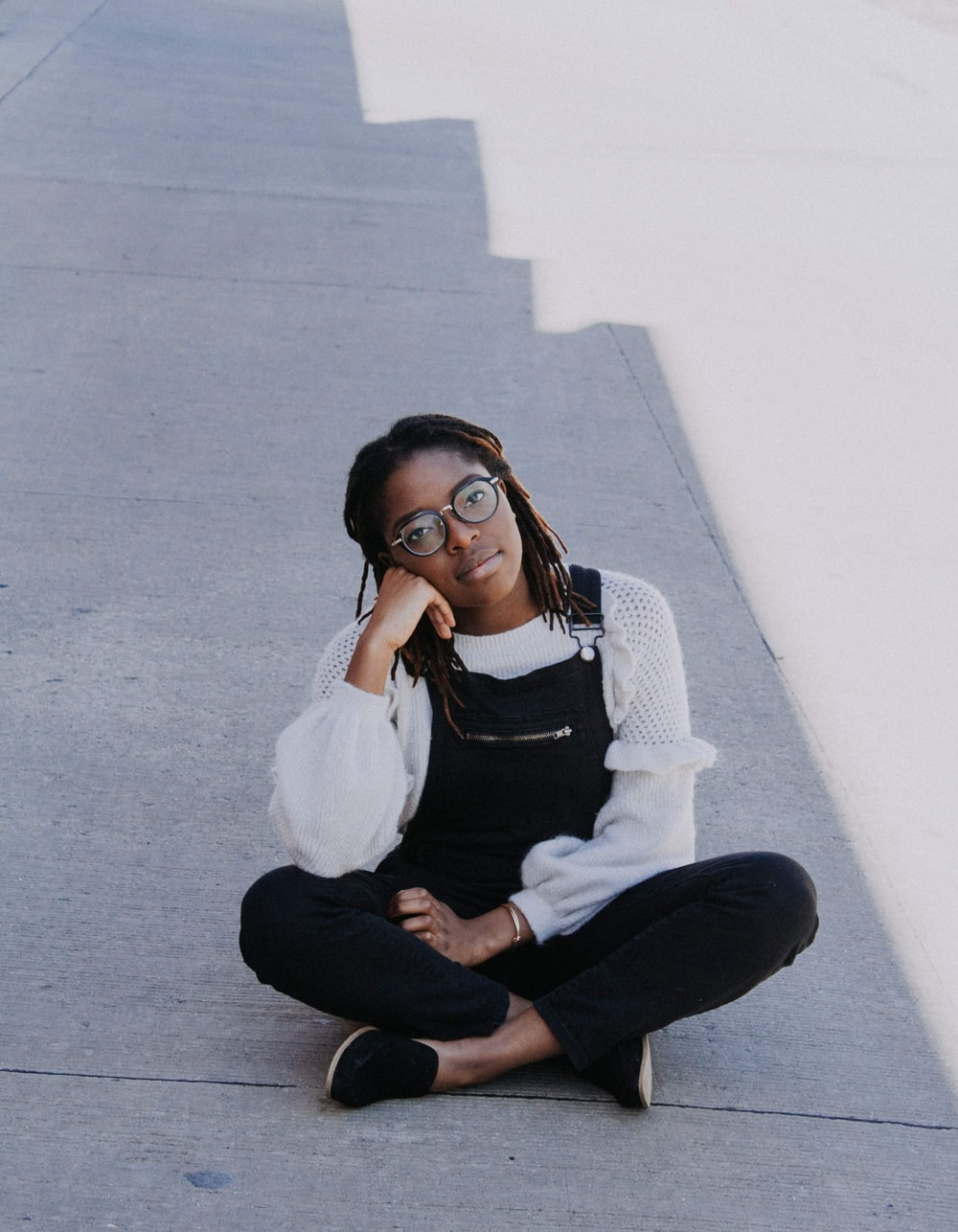 woman in overall pants sitting on pavement