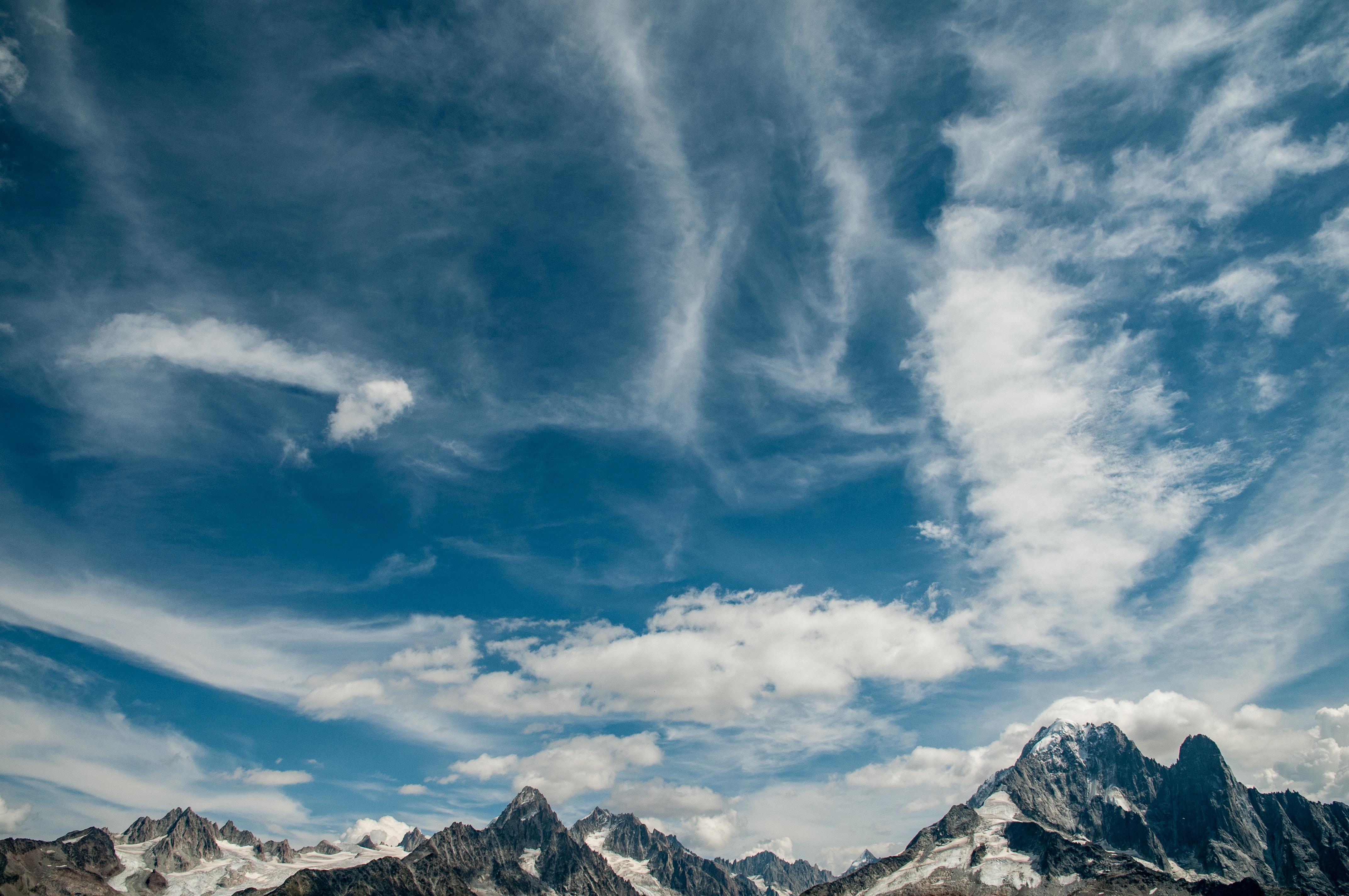 mountain under cirrus clouds during daytime
