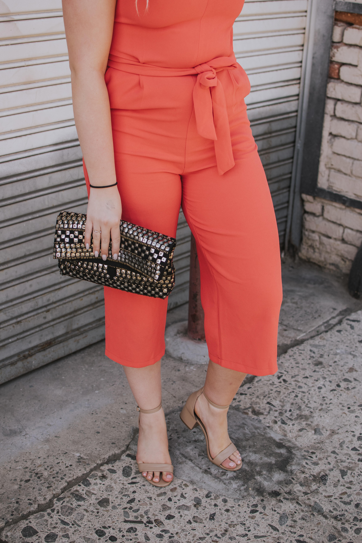 woman in orange jumpsuit holding clutch bag