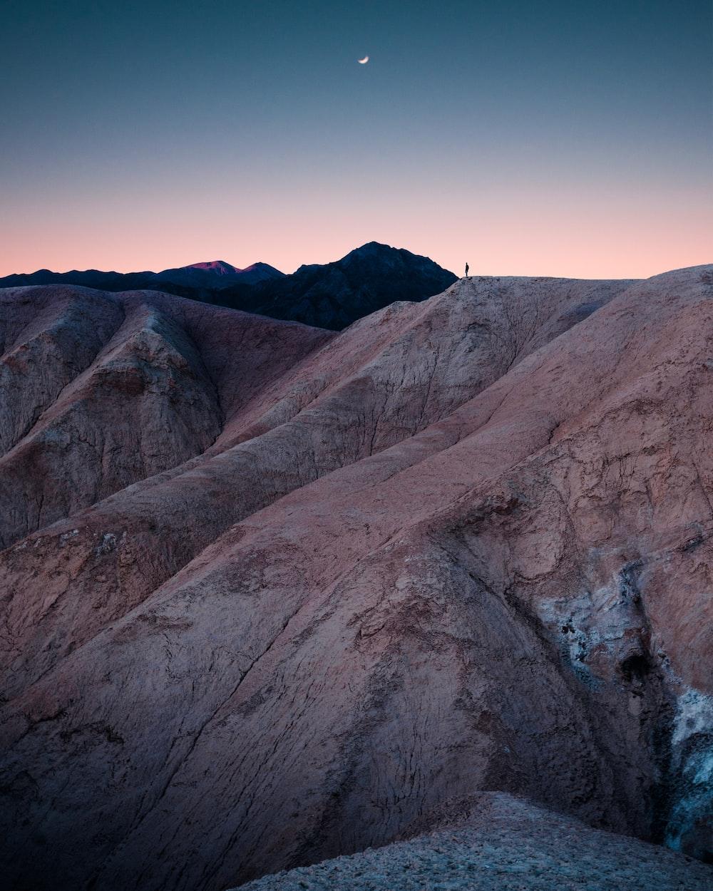 man standing on mountain during daytime