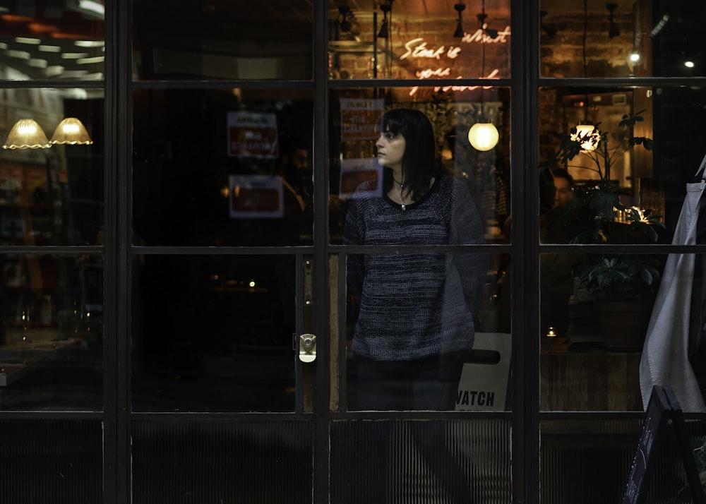 woman standing near glass window