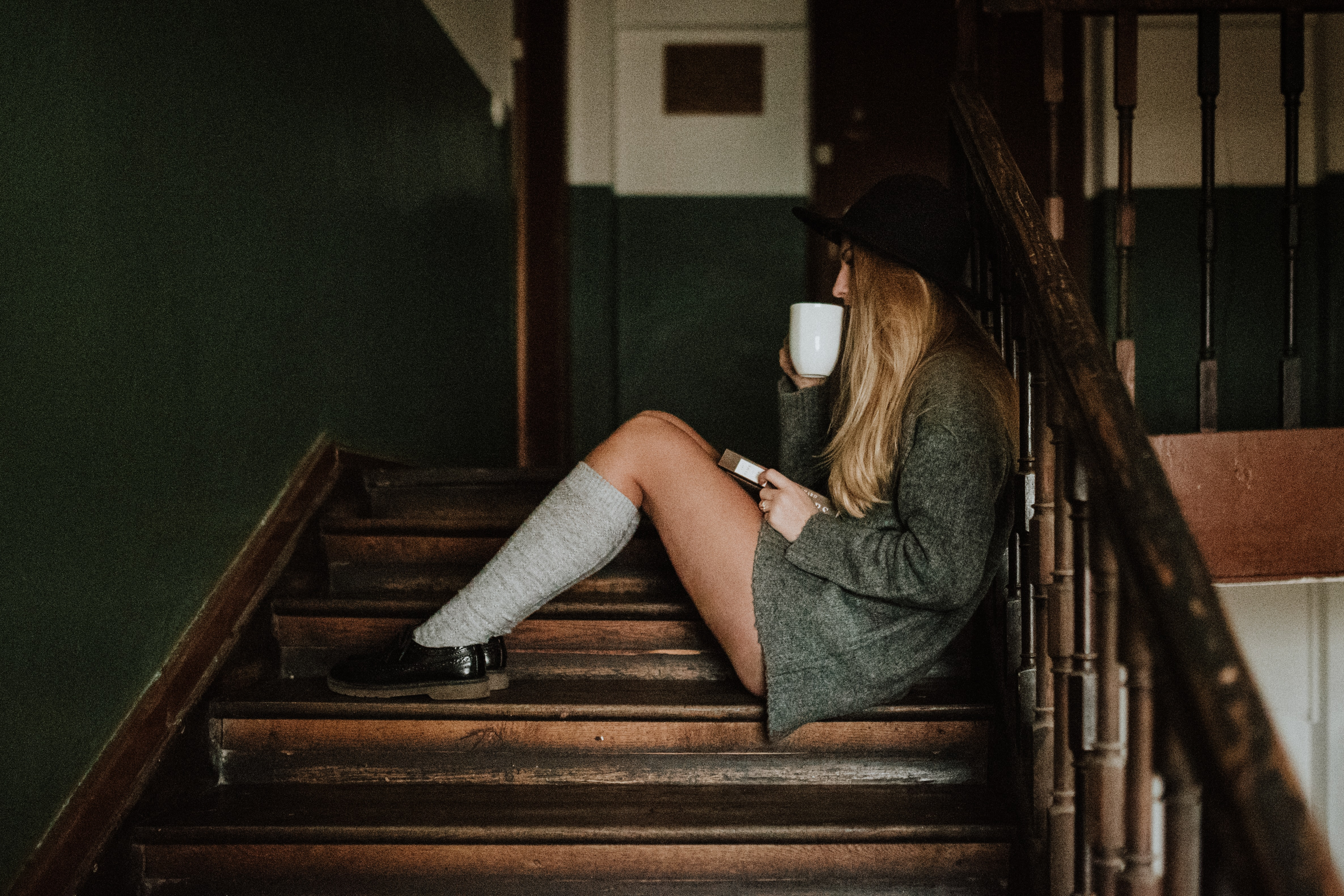 woman sitting on brown wooden stairs while drinking