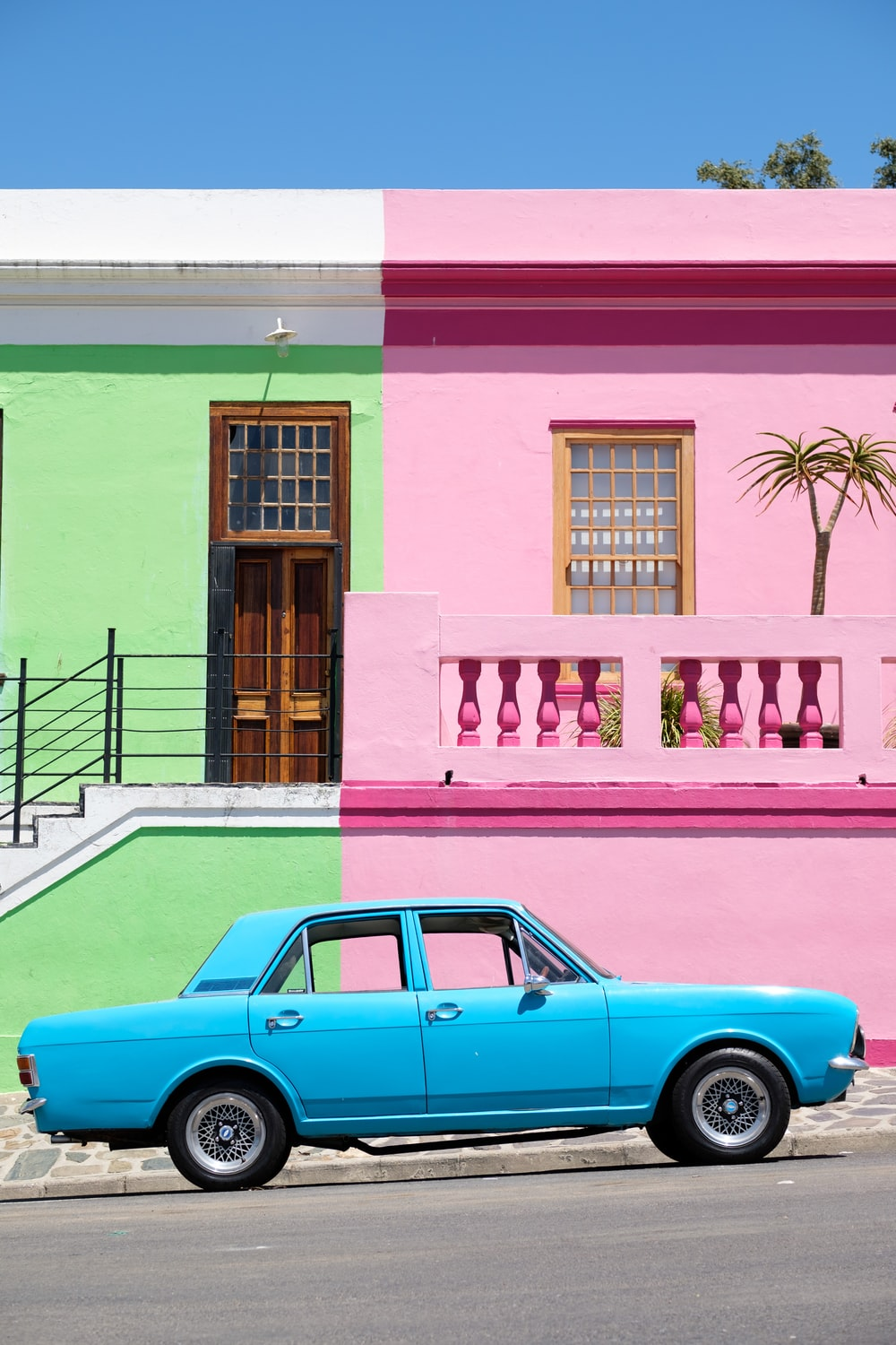 blue sedan parked beside pink and green house
