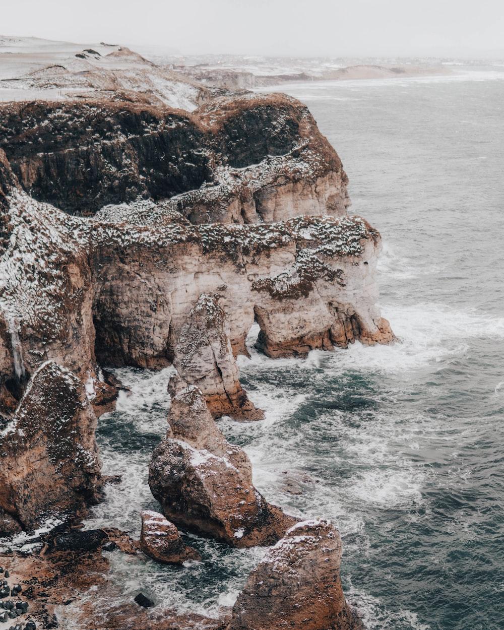 high angle photo of mountain rocks beside sea