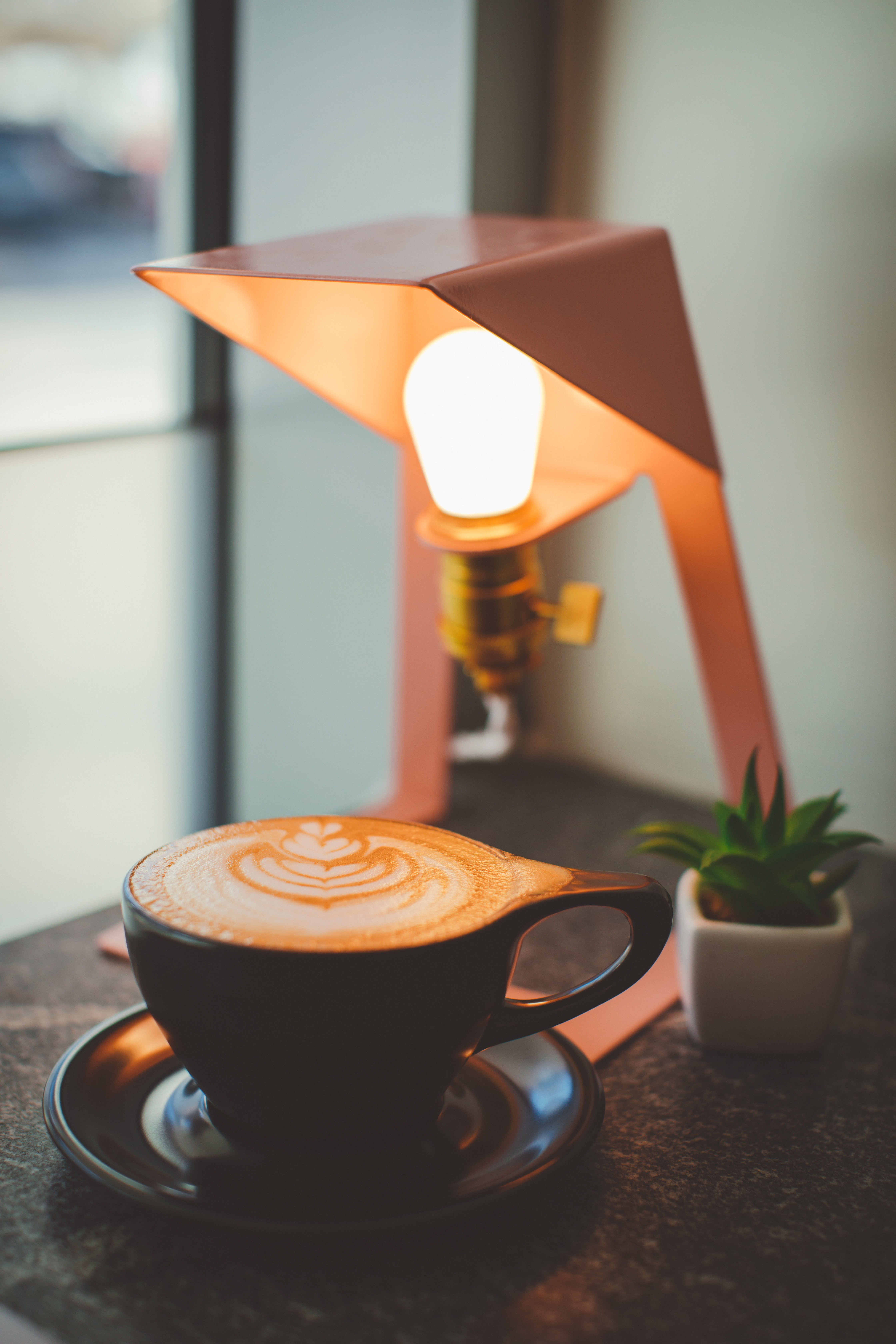 cup of cappuccino near table lamp
