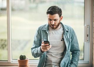 man holding a smartphone near the window