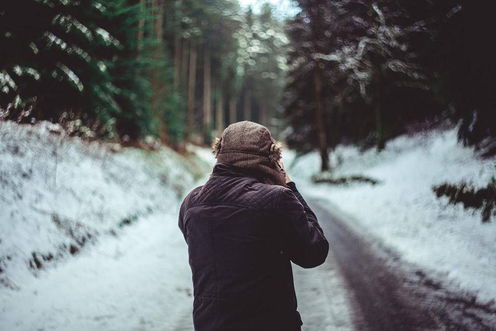 man in brown jacket standing between trees