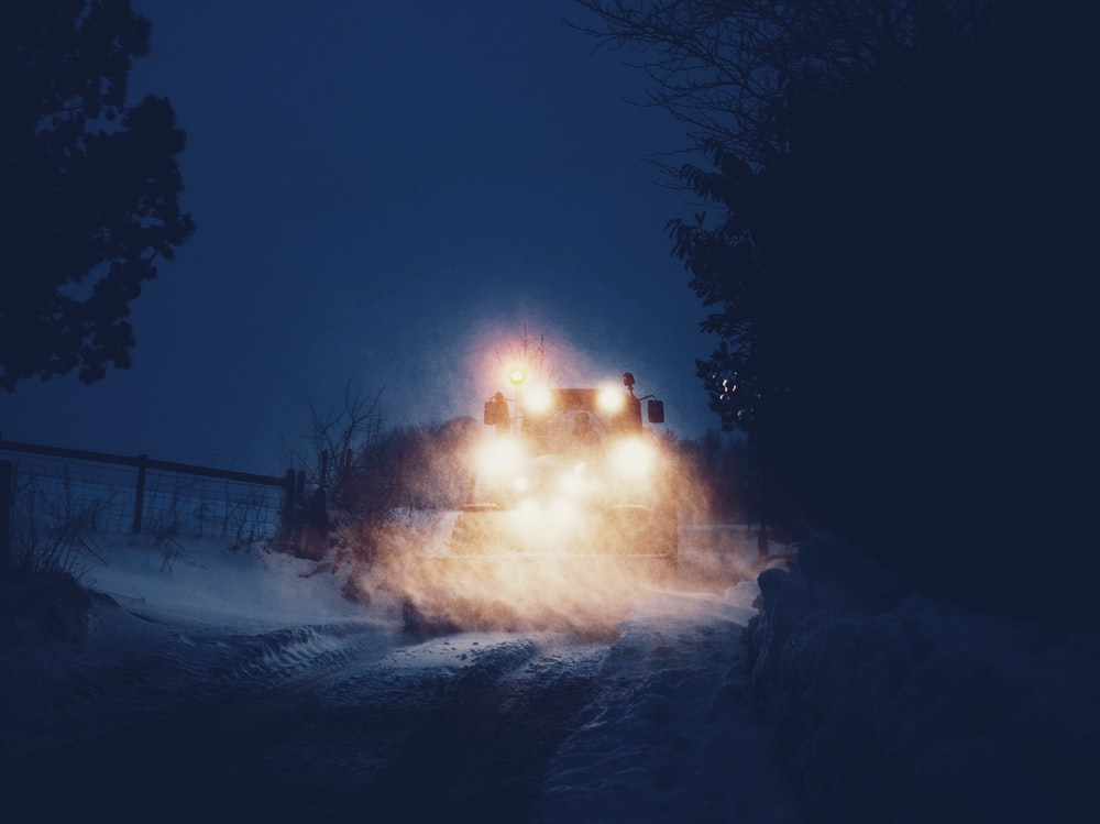 vehicle on snow covered road at nighttime