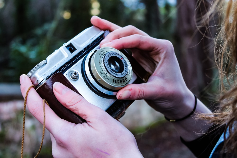 person holding point-and-shoot camera adjusting a lens