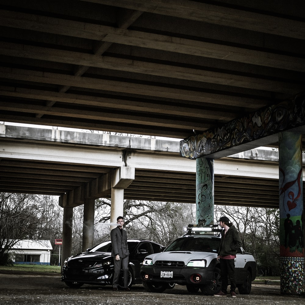 two man standing near cars