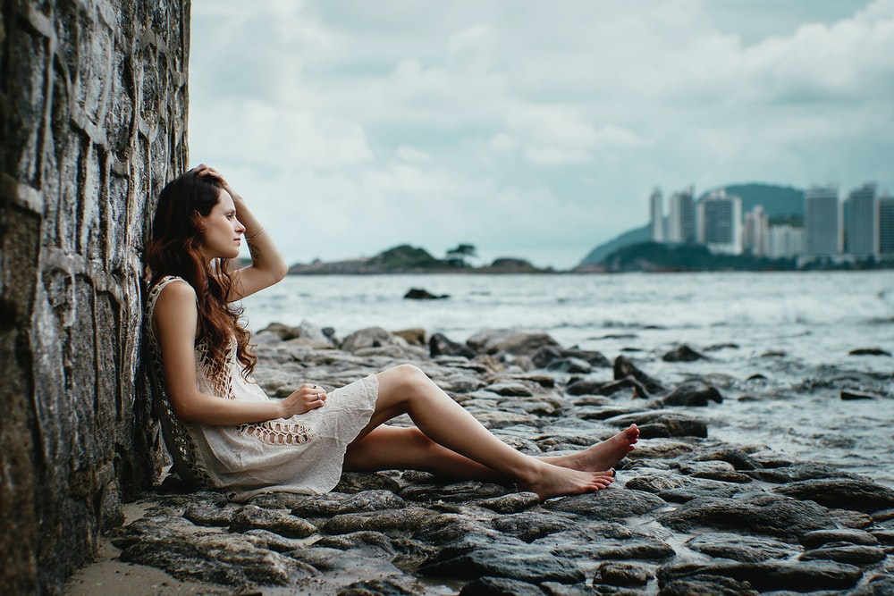 woman leaning on stone wall near body of water