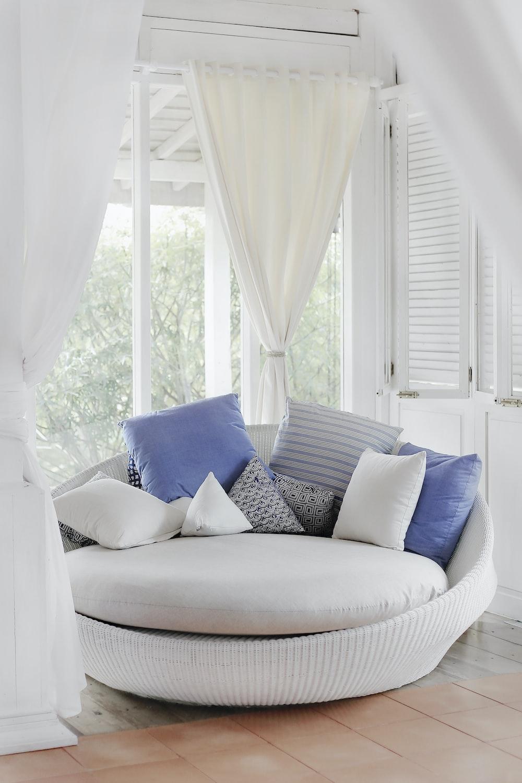 white cuddle chair and throw pillows near window