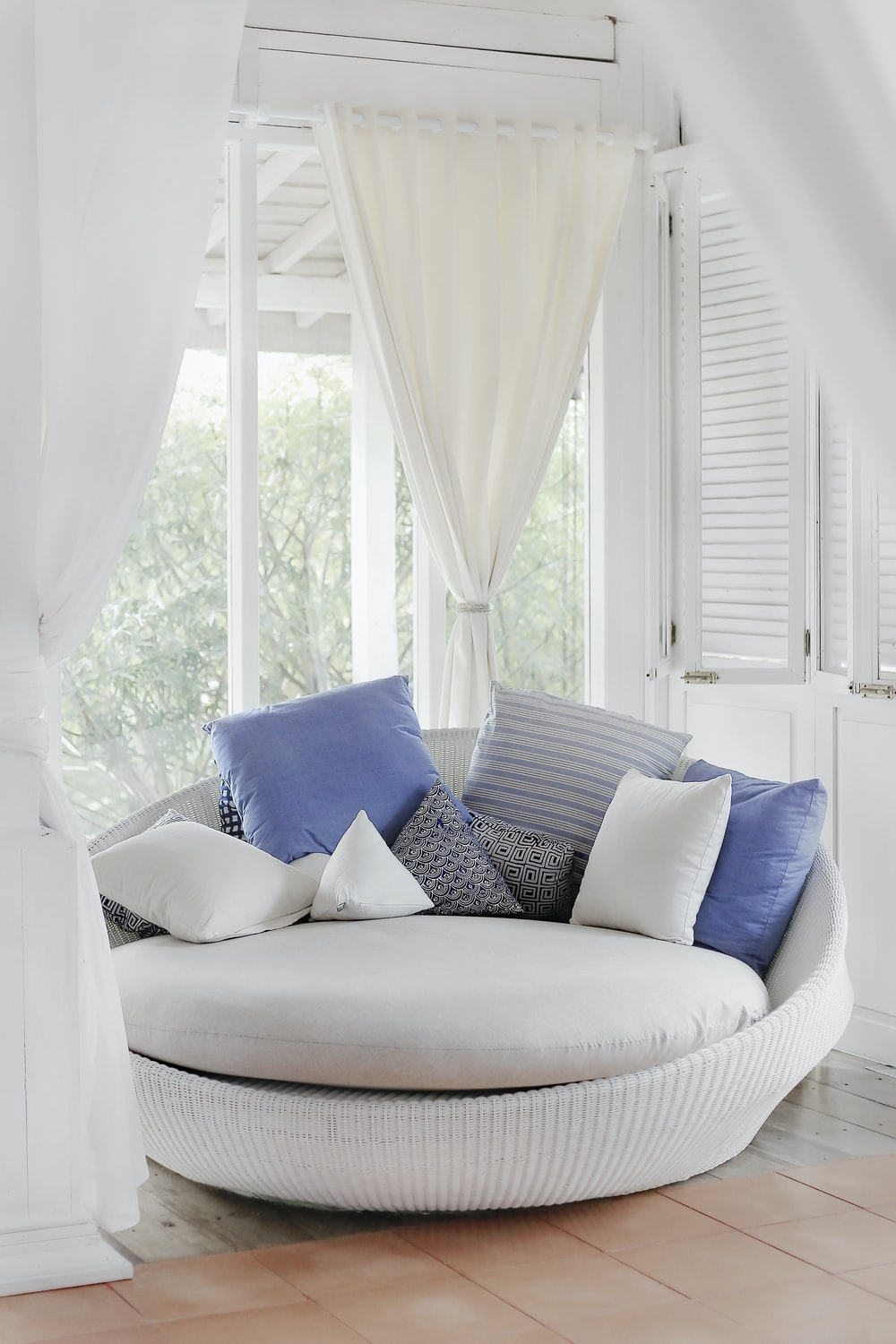 white cuddle chair and throw pillows near window
