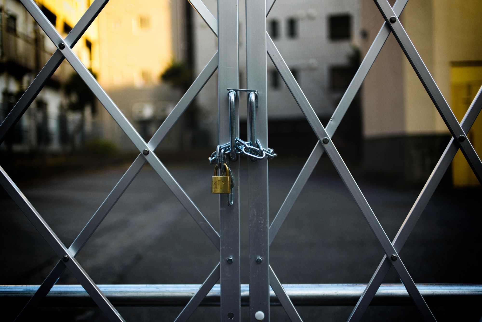 A padlock and chain are used to close a metal gate.