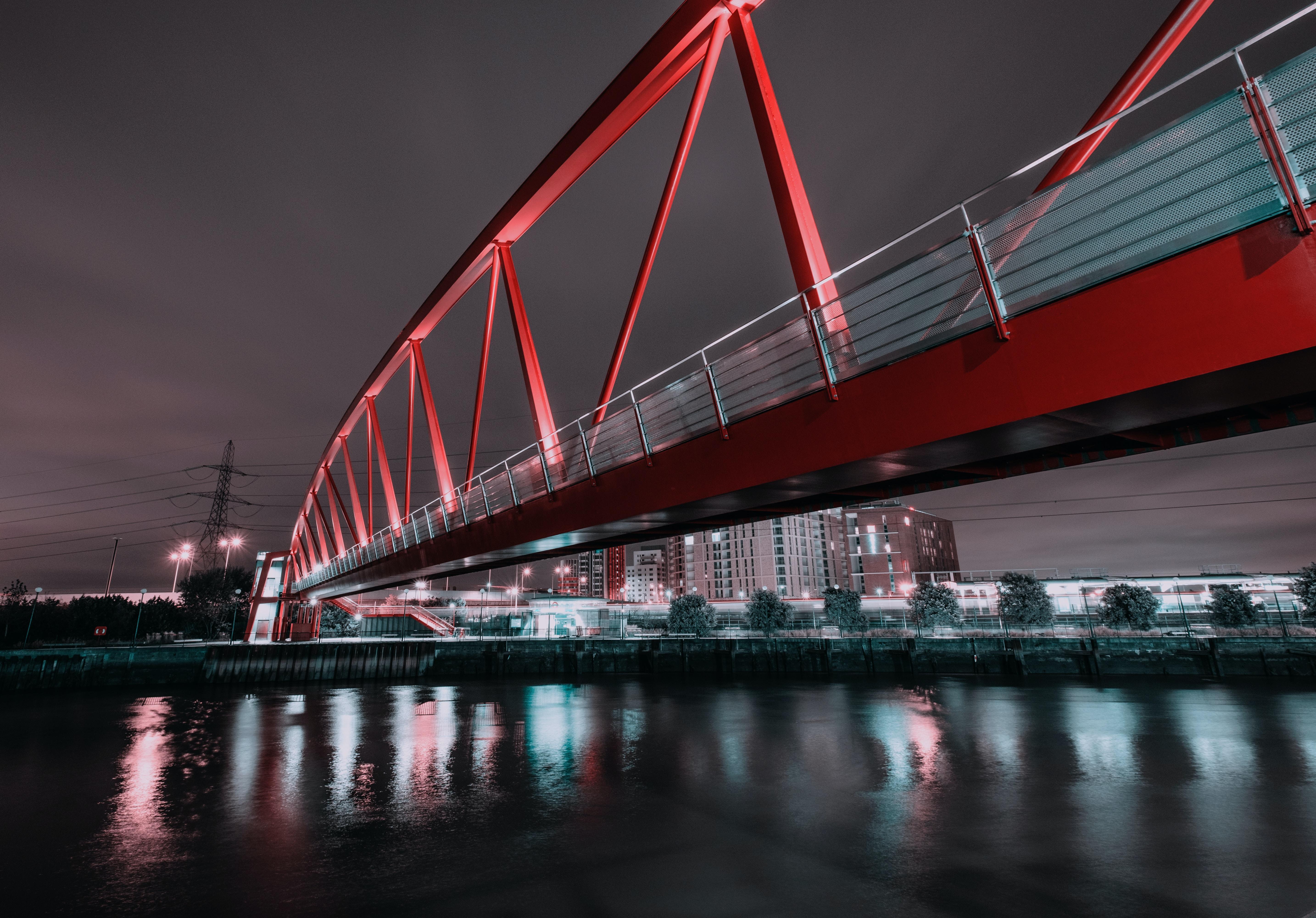 red truss bridge over body of water