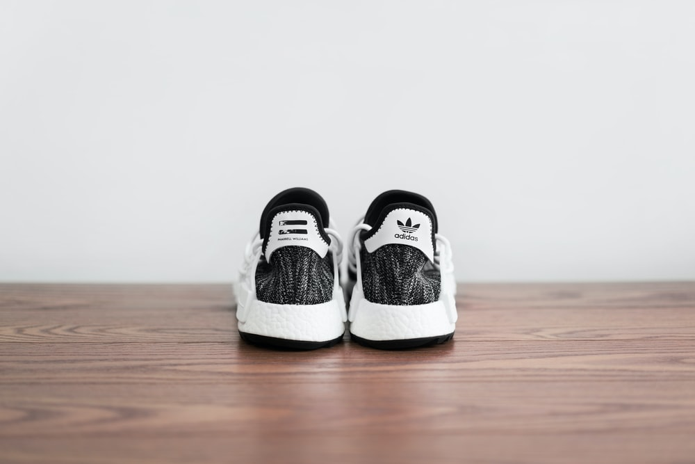 pair of white-and-black adidas shoes on wooden surface