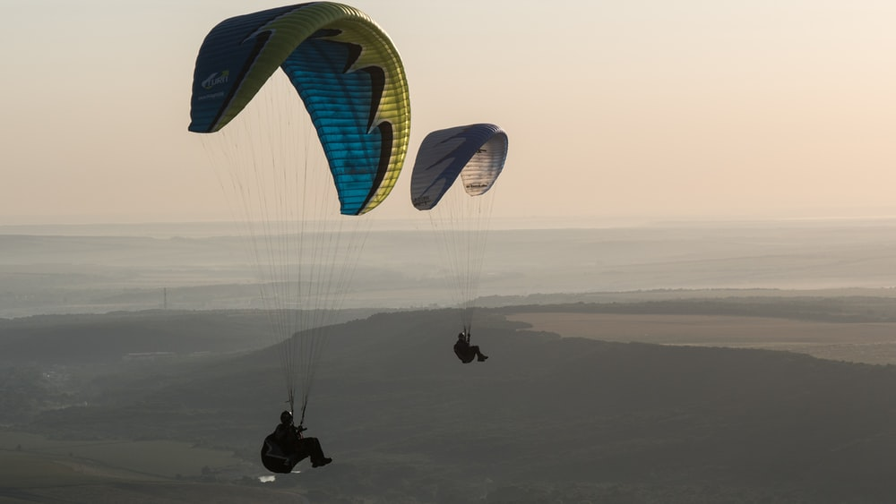 time-lapse photo of two people parachuting during daytime